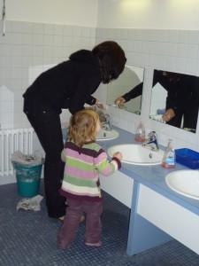 gebückte Haltung am Waschbecken in der Kita